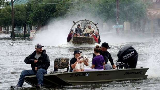 People are rescued from flood waters from Hurricane Harvey on an air boat in Dickinson, Texas, on Aug. 27.