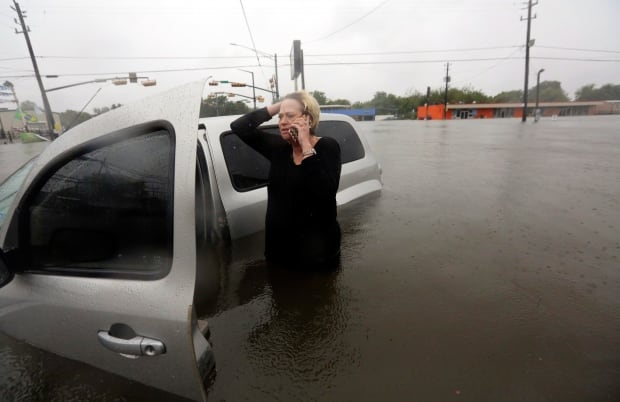 Rhonda Worthington talks on her cell phone with a 911 dispatcher after her car become stuck in rising floodwaters. (The Associated Press)