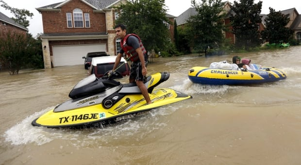 Flood victims are towed to safety by a jet ski as floodwaters from Tropical Storm Harvey rise Monday. (David J. Phillip/Associated Press)