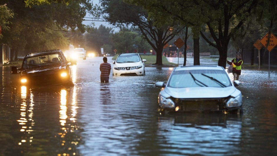 Vehicles are abandoned along flooded Dairy Ashford Drive in Houston, Texas, on Monday.