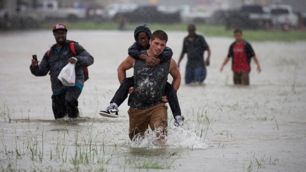 A man wades through floodwaters from tropical storm Harvey while helping a boy in East Houston on Monday. Water levels have broken records in the state.