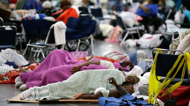 People sleep on the floor at the George R. Brown Convention Center, which has been set up as a shelter for evacuees from floodwaters in Houston.  Officials say more than 5,000 people have taken refuge in shelters due to the disaster.