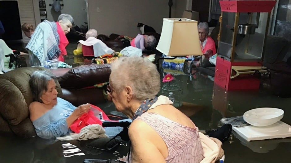Residents of the La Vita Bella nursing home in Dickinson, Texas, sit in waist-deep flood waters caused by Hurricane Harvey on Sunday. Authorities said all the residents were safely evacuated from the facility. Trudy Lampson/Associated Press