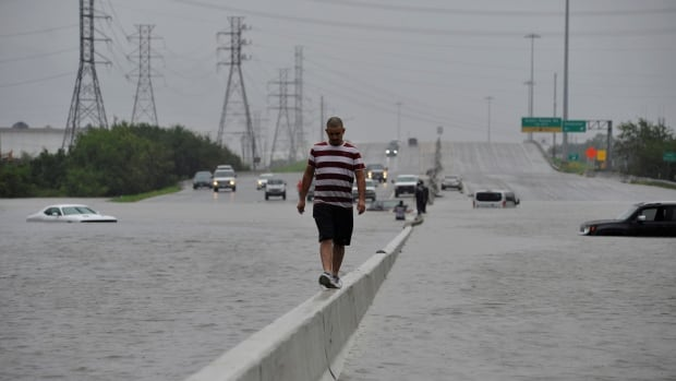 A stranded motorist escapes floodwaters on Interstate 225 after Hurricane Harvey inundated the Texas Gulf coast with rain causing mass flooding, in Houston on Sunday.