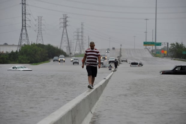 A stranded motorist escapes floodwaters on Interstate 225 after Hurricane Harvey inundated the Texas Gulf Coast with rain causing mass flooding, in Houston ...