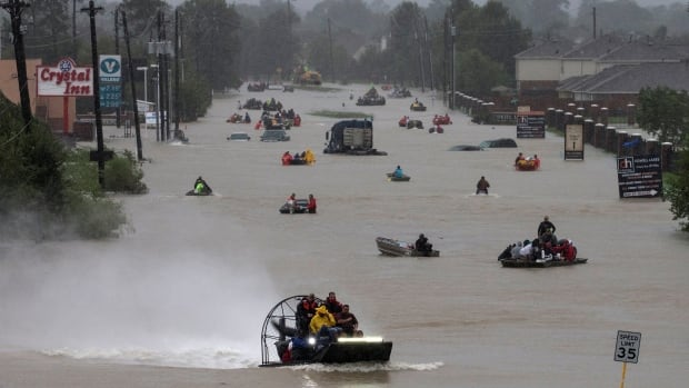 Residents use boats to evacuate flood waters from Tropical Storm Harvey. A new study suggests that this type of flooding could become more common in the wake of climate change.