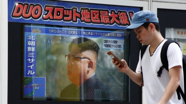 "A man walks past a TV set showing North Korea's leader Kim Jong-un in a news report about North Korea's missile launch in Tokyo, on Tuesday. Kim said the launch was a ""prelude"" to containing the U.S. territory of Guam."