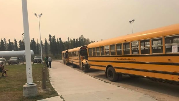 Buses wait to transport Pelican Narrows residents to other communities.