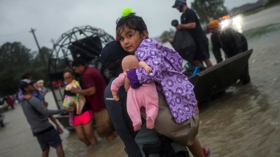 A woman holds a girl as her family arrives to high ground by boat due to floods in Houston. August 28, 2017.