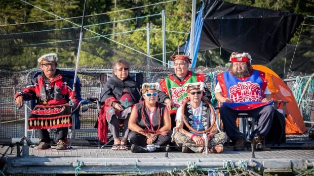 Protesters gather at the Marine Harvest fish farm on Swanson Island, near Alert Bay, B.C., in a handout photo from the Facebook page Swanson Occupation. Ernest Alfred, 36, sitting cross-legged on the right wearing a cedar bark neck ring, sits with other traditional leaders from neighbouring villages.