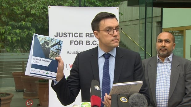 Josh Paterson, with the B.C. Civil Liberties Association, holds up a report compiled by the group that details recommendations it's making to the province.