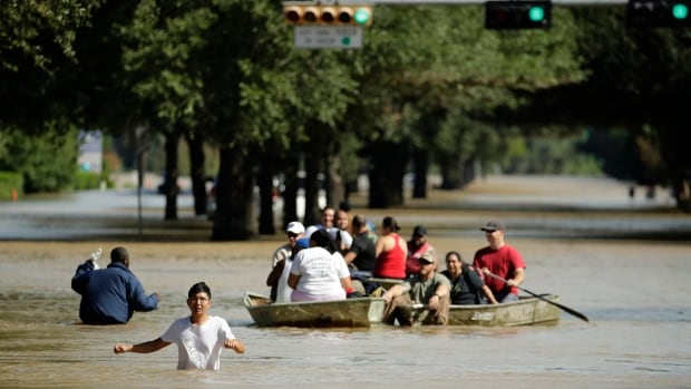 People evacuate a Houston neighbourhood inundated after water was released from nearby Addicks Reservoir when it reached capacity due to tropical storm Harvey on Wednesday. A recent Trump order could force Houston and other cities to rebuild hospitals and highways in the same way and in the same flood-prone areas.