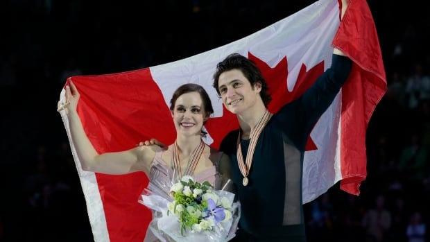 Canadian Tessa Virtue and Scott Moir show off their gold medals at the world figure skating championship in March, a pose they are hoping to duplicate at the PyeongChang Olympics in February.