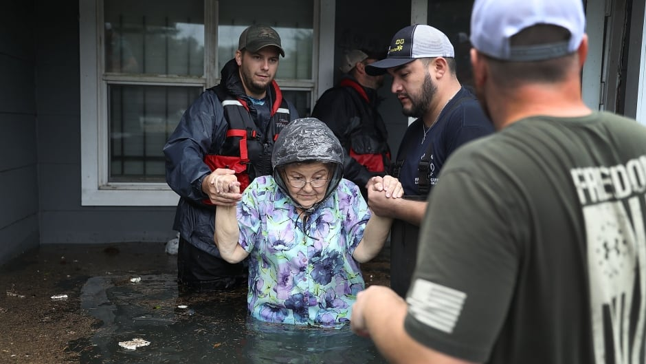 August 30, 2017 - A woman is helped from her flooded home in Port Arthur Texas, by volunteers.