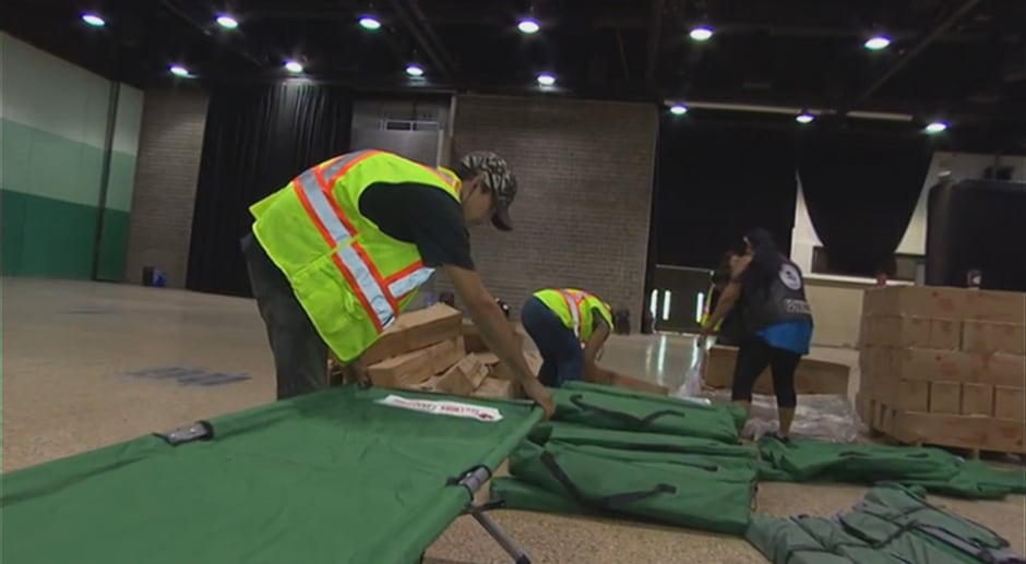 Volunteers set up cots in Winnipeg Convention Centre for fire evacuees