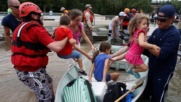 People unload children to cross a bridge as they evacuate from the rising waters of Buffalo Bayou following Hurricane Harvey in a neighbourhood west of Houston. Canada will help the U.S. recovery efforts with supplies, after a phone call between Justin Trudeau and Donald Trump.