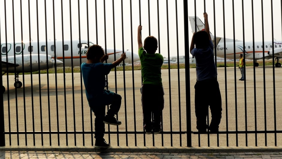 Kids clamber up a fence as rescue planes from Perimeter Aviation land in St. Theresa Point, Man.