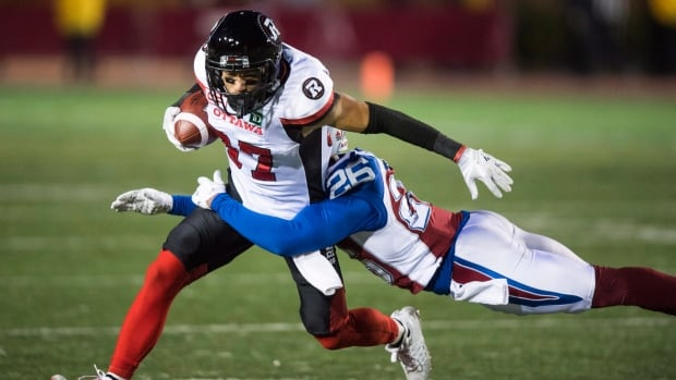 Redblacks receiver Joshua Stangby is tackled by Montreal defensive back Tyree Hollins during Ottawa's 32-4 win Thursday in Montreal.