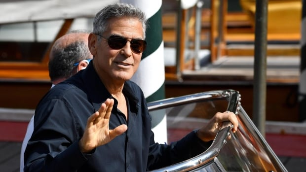 Actor George Clooney waves to photographers as he arrives on a motorboat during the 74th edition of the Venice Film Festival, in Venice, Italy, Saturday, Sept. 2, 2017.