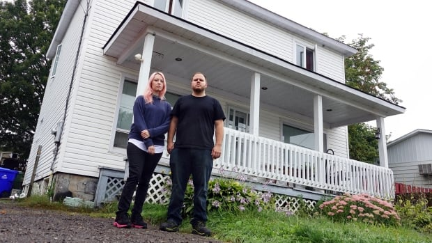 Amanda Larabee and Patrick Dawson stand outside their flood-damaged home on Rue Glaude in Gatineau on Sept. 3, 2017.