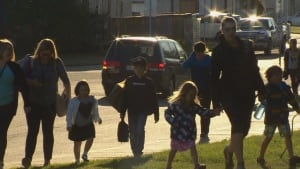 Kids and parents walk to St. Kateri Catholic School on the first day of class