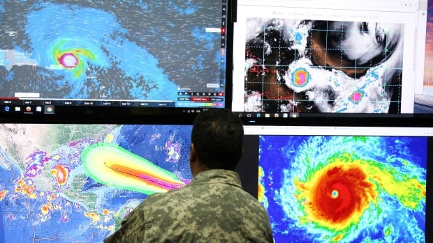 A member of the Emergency Operations Committee monitors the trajectory of Hurricane Irma in Santo Domingo, Dominican Republic, on Tuesday.