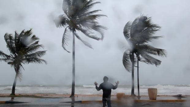 A man stands in the wind and rain in Luquillo, Puerto Rico, as Hurricane Irma slams across islands in the northern Caribbean on Wednesday. Irma set an Atlantic Ocean wind record, but the size of the hurricane and its forward speed could say more about its ultimate impact.