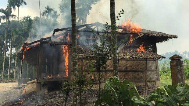 Houses were on fire in Gawdu Zara village, northern Rakhine state, Myanmar, on Thursday. Journalists saw new fires burning in the Myanmar village that had been abandoned by Rohingya Muslims, and where pages from Islamic texts were seen ripped and left on the ground.