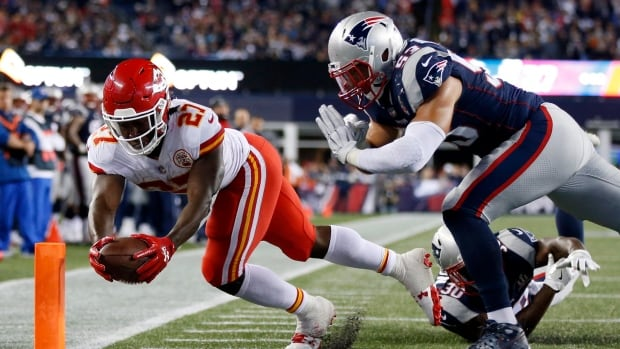 Kansas City Chiefs running back Kareem Hunt, left, crosses the goal line to score a touchdown against the New England Patriots during the second half on Thursday in Foxborough, Mass.