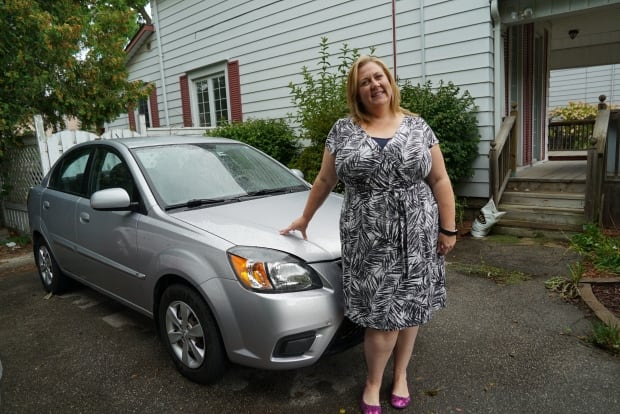 Tammy stands with her car