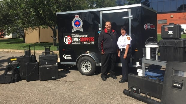 Shawn Peremesko, the chair of the Thunder Bay District Crimestoppers, stands with Sylvie Hauth, acting chief of the Thunder Bay Police Service, in front of the new trailer the group donated to the force. It will be used to store and transport the equipment used in critical incidents.