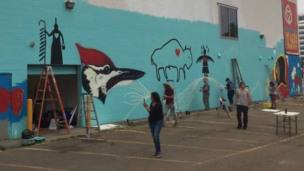 Artist Isaac Murdoch, from Serpent River First Nation in Ontario, and volunteers in Edmonton began painting a mural on the iHuman Youth Society building on Friday. The mural is about protecting water from threats posed by industrial development and pipelines, Murdoch said.