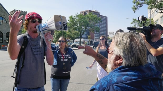 An organizer of the Stand Against Canadian Fake News Corporations event, organized by the group Winnipeg Alternative Media, yells in a megaphone to people gathered for the Winnipeg Diversity Rally Against Hate.
