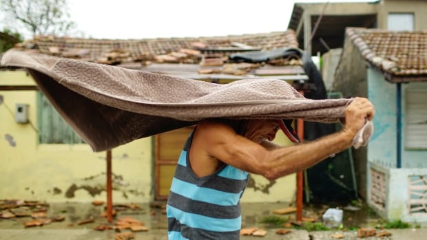 A man shelters himself against the rain after the passage of Hurricane Irma in Caibarien, Cuba on Saturday, Sept. 9, 2017.