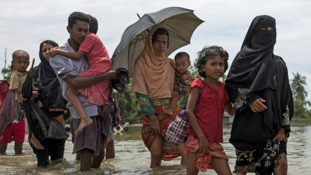 Rohingya Muslim refugees wade through water after arriving by boat from Myanmar on Friday in Dakhinpara, Bangladesh.