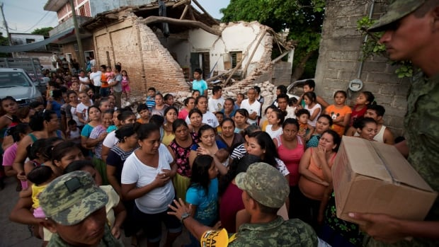 Soldiers try to organize a crowd as they hand out rations to people in a zone heavily affected by last Thursday's massive earthquake, in Juchitan, Oaxaca state.