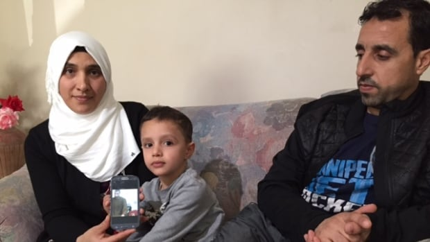 Magda (left) and Muhamd Asliman say they're grateful to be in Winnipeg with their children, but feel powerless to help those they left back home in Syria.  In front of their 4-year-old son Ahmed, Magda holds a photo of Muhamd's brother Fahdi, who died.