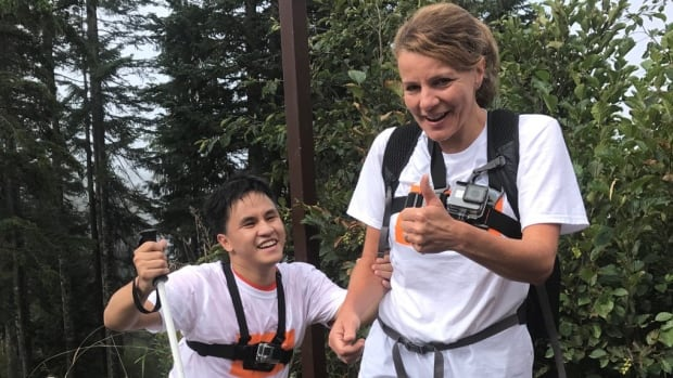 Hiker Clement Chou (left) holds onto his guide Christina Duncan (right) as they summit the Grouse Grind.