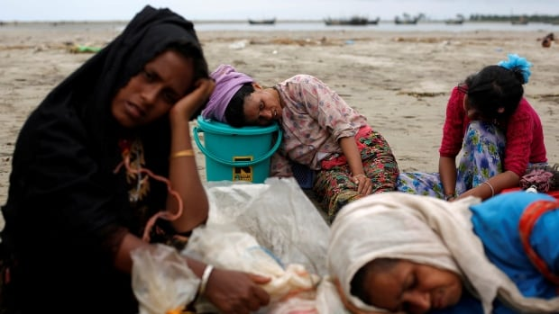 Exhausted Rohingya refugees rest on the shore after crossing the Bangladesh-Myanmar border by boat through the Bay of Bengal in Shah Porir Dwip, Bangladesh, on Sunday.