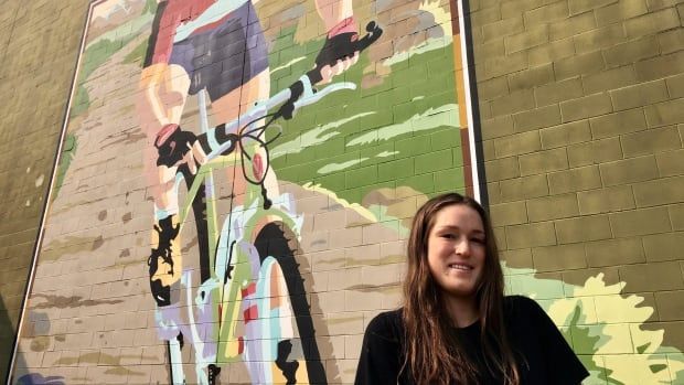 Lea McCroy, 17, poses for a photo in front of a Canmore mural in memory of her mom, Isabelle Dube, who was killed in a grizzly bear attack in June 2005.