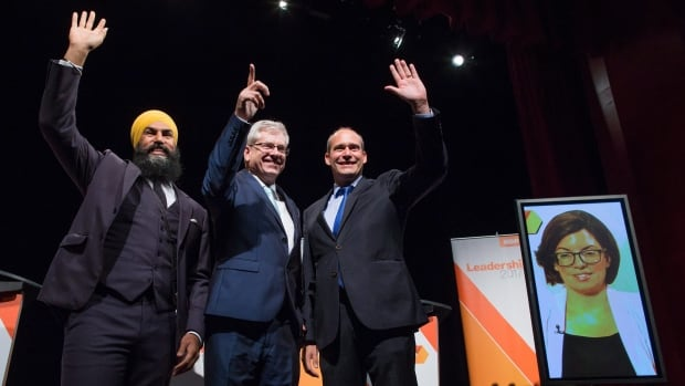 From left: Jagmeet Singh, Charlie Angus and Guy Caron pose for a photograph as Niki Ashton is seen on a screen via satellite from Ottawa, before the final federal NDP leadership debate in Vancouver Sept. 10. Online voting begins today with first-round results announced Oct. 1.