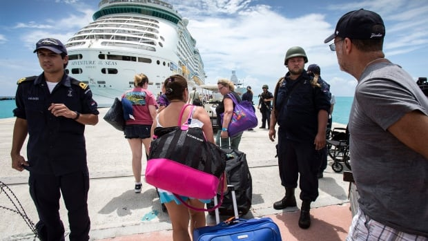 This photo provided by the Dutch defence ministry on Sunday, shows people walking toward a cruise ship anchored on Dutch side of Saint Martin, after the passage of Hurricane Irma.