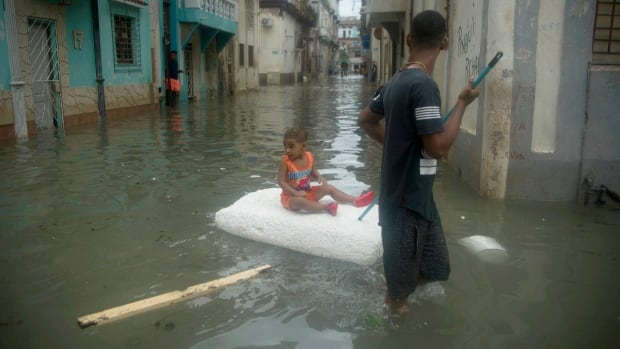A young man floats a girl on a block of styrofoam through a flooded street in Havana on Sunday after Hurricane Irma ripped roofs off houses, collapsed buildings and flooded hundreds of kilometres of coastline after cutting a trail of destruction across the Caribbean.