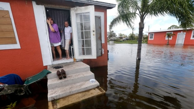 Quintana and Liz Perez look out at the flooding outside their home in the aftermath of Hurricane Irma in Immokalee, Fla.