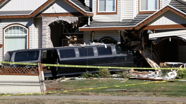 A limousine was left in position after smashing through the front of a Surrey home, because fire officials believed it was bearing the home's weight after knocking out posts and walls.