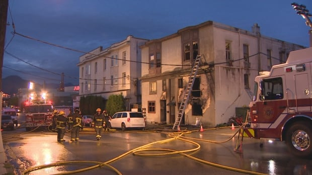 Firefighters clean up after a fire at a 24-unit building in East Vancouver on Monday.