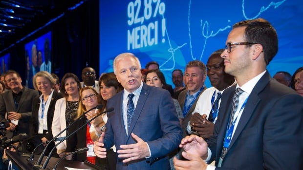 Jean-François Lisée, centre, speaks to delegates after the result of his confidence vote was announced on Saturday.