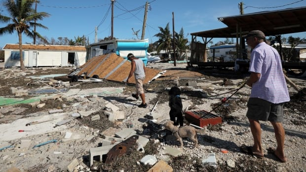 Local residents walk along a destroyed trailer park in Plantation Key in the Florida Keys on Tuesday.  Several airlines plan to resume travel to Florida this week.