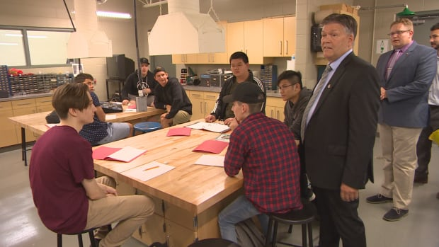 Education and Training Minister Ian Wishart stands with students in a new addition to Garden City Collegiate on Tuesday.