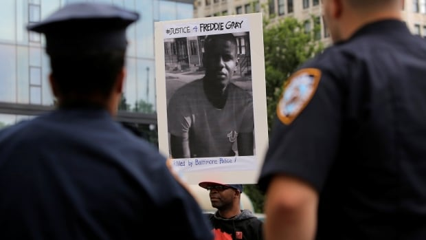 A man holding a sign with a photo of Freddie Gray participates in a protest in New York in June 2016.